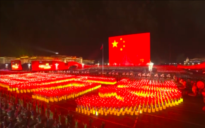 China's 70th Anniversary display on giant led screen China red flag and people on front red costume